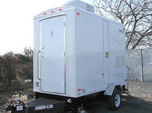 A compact 2 stall white portable restroom trailer.