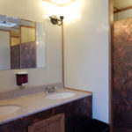 Interior Photo of Moen's 6 Stall VIP Restroom Trailer showing a 2 sink vanity with mirror, lights, and soap dispenser.