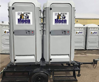 Two grey VIP portable flushing toilets sitting on a black trailer with wheels