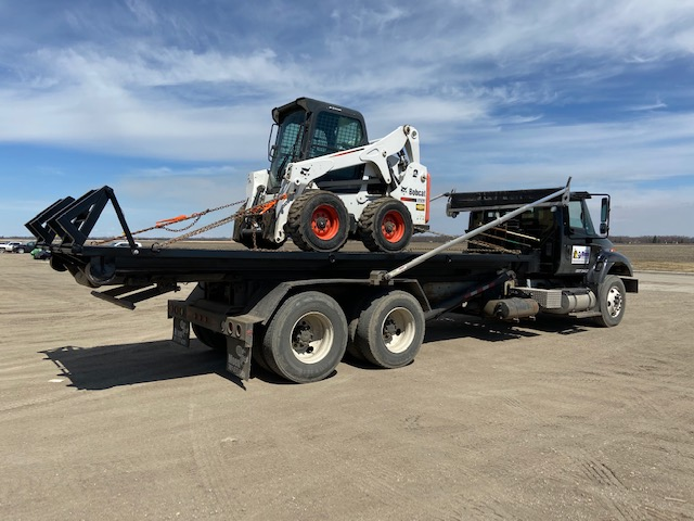 Image showing a Moen truck hauling a skid steer.